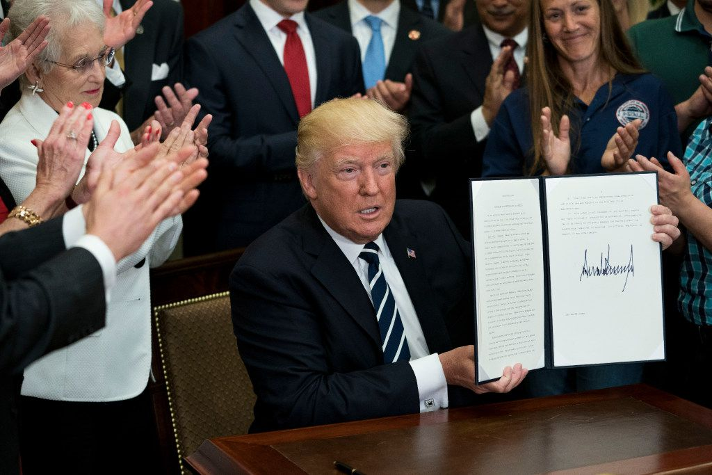 President Donald Trump holds up an executive order he signed for the Apprenticeship and Workforce of Tomorrow program on June 15.