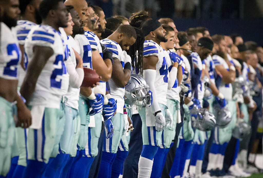 Dallas Cowboys players stand for the national anthem before an NFL football game against the Philadelphia Eagles at AT&T Stadium on Sunday, Oct. 30, 2016, in Arlington. (Smiley N. Pool/The Dallas Morning News)