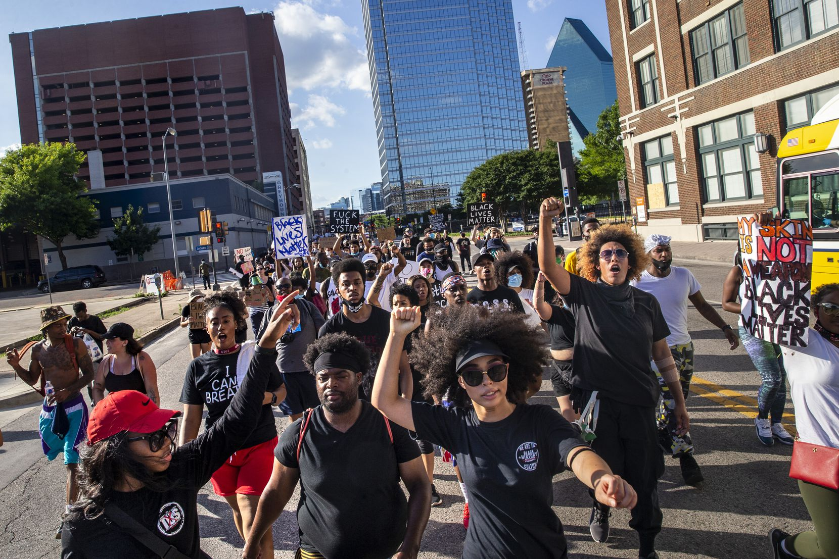 Tierra Jenae Giles (center) leads protesters as they march in a demonstration denouncing police brutality and systemic racism in Dallas on Thursday.
