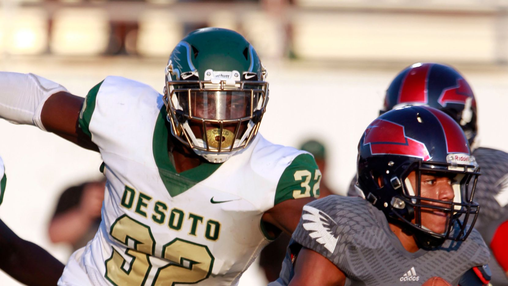 FILE - DeSoto defensive lineman Shemar Turner (32) chases down Bishop Dunne quarterback Simeon Evans (1) during a game at Sprague Stadium in Dallas on Saturday, Sept. 14, 2019.
