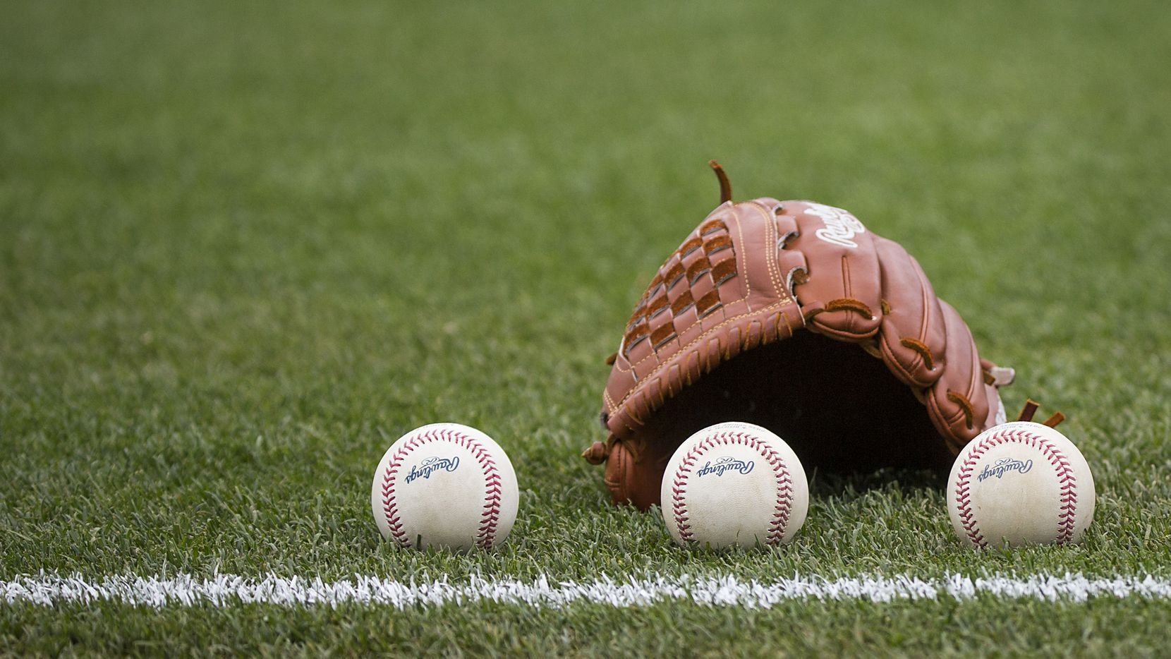 Balls rest next to the glove of before a Texas Rangers spring training game against the Seattle Mariners at Surprise Stadium on Sunday, March 6, 2016, in Surprise, Ariz.