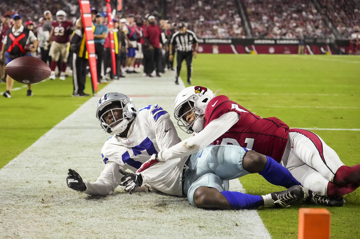 Dallas Cowboys wide receiver Malik Turner (17) is injured on a pass play as Arizona Cardinals cornerback Tay Gowan (32) comes down on his left ankle during the second half of a preseason NFL football game at State Farm Stadium on Friday, Aug. 13, 2021, in Glendale, Ariz.