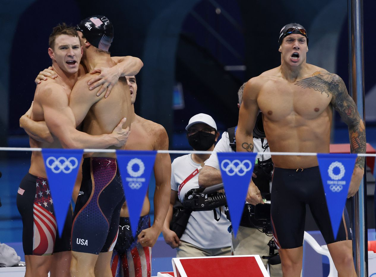 USA's Ryan Murphy hugs Zach Apple as Michael Andrew and Caeleb Dressel celebrate setting a new world record in the men's 4x100 meter medley relay final during the postponed 2020 Tokyo Olympics at Tokyo Aquatics Centre, on Sunday, August 1, 2021, in Tokyo, Japan. USA earned a gold medal, setting a new world record with a time of 3:26.78. (Vernon Bryant/The Dallas Morning News)