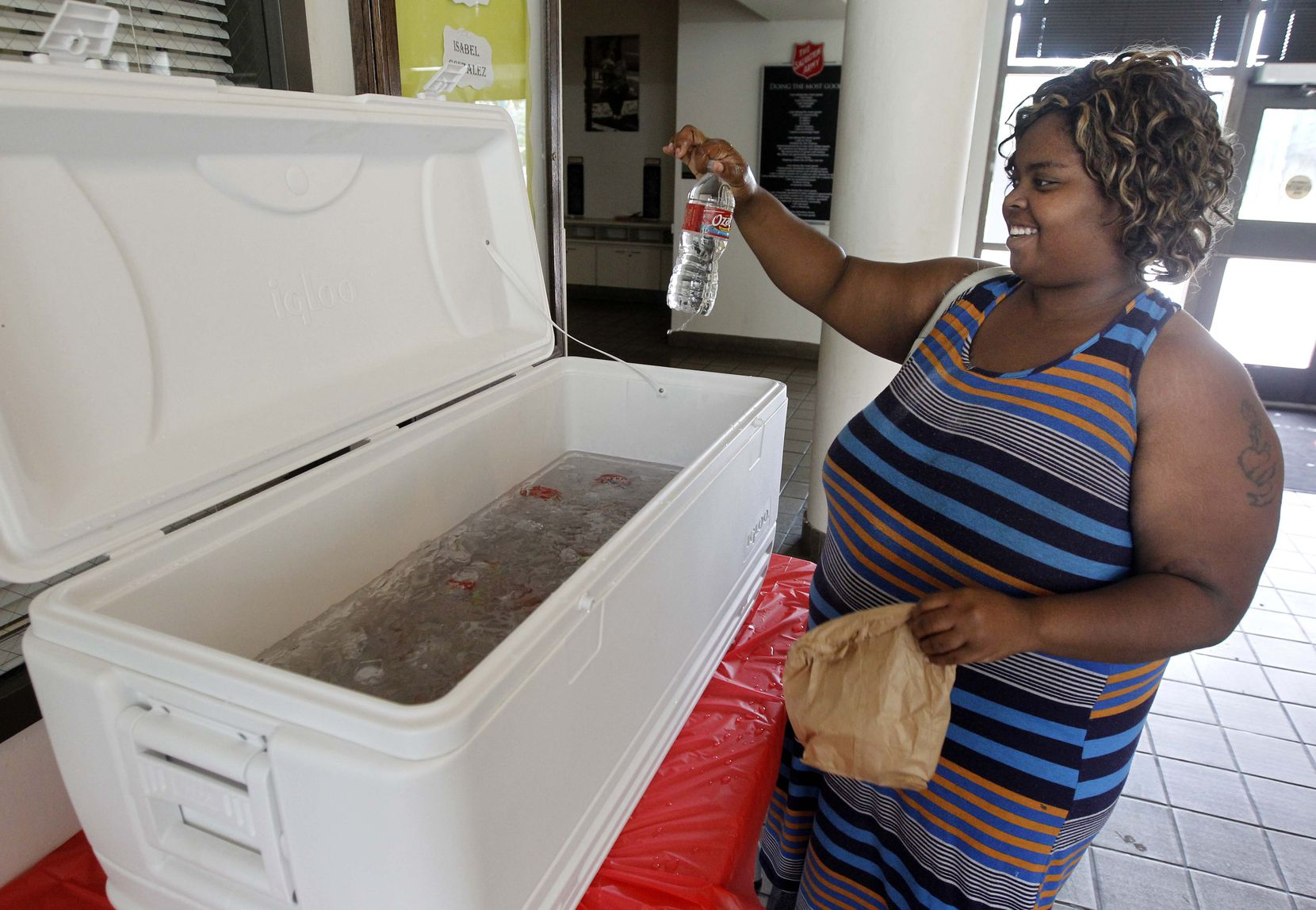 Ashley Ellis grabs an bottle of water at a cooling center at the Salvation Army's Carr  P. Collins Center at 5302 Harry Hines Blvd in Dallas.