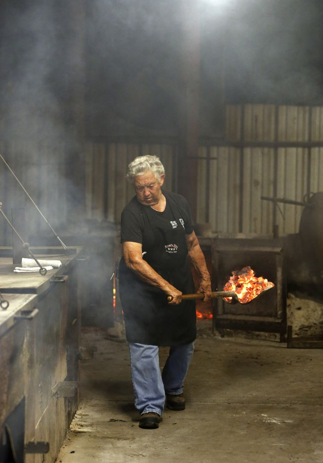 Tootsie Tomanetz makes her way between barbecue pits hauling hot coals.