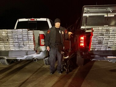 Lewisville police Officer Pat Robey and his canine partner, Stryker, stand with nearly 600 pounds of methamphetamine the department seized on Sunday.