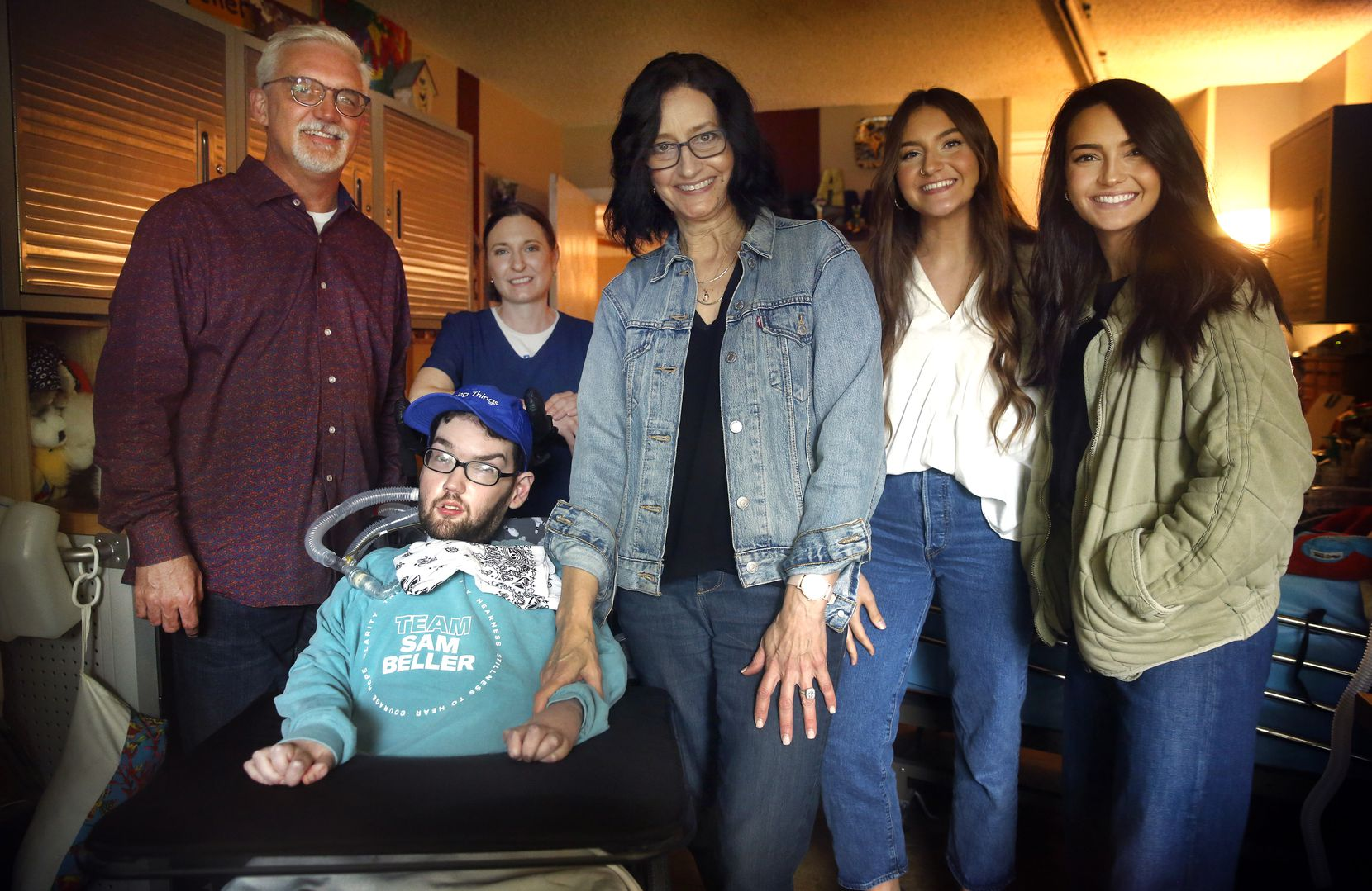 Sam Beller in his room at home with (from left) his father David, nurse Michelle Erving, mother Kelly, and sisters Simone and Tevah. For families like the Bellers, caring for loved ones most at risk of dying from complications of COVID-19, every day feels like a fight.