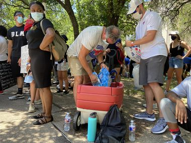 SMU football coach Sonny Dykes passes out water bottles while attending a protest at Dallas City Hall on Friday, June 5, 2020.