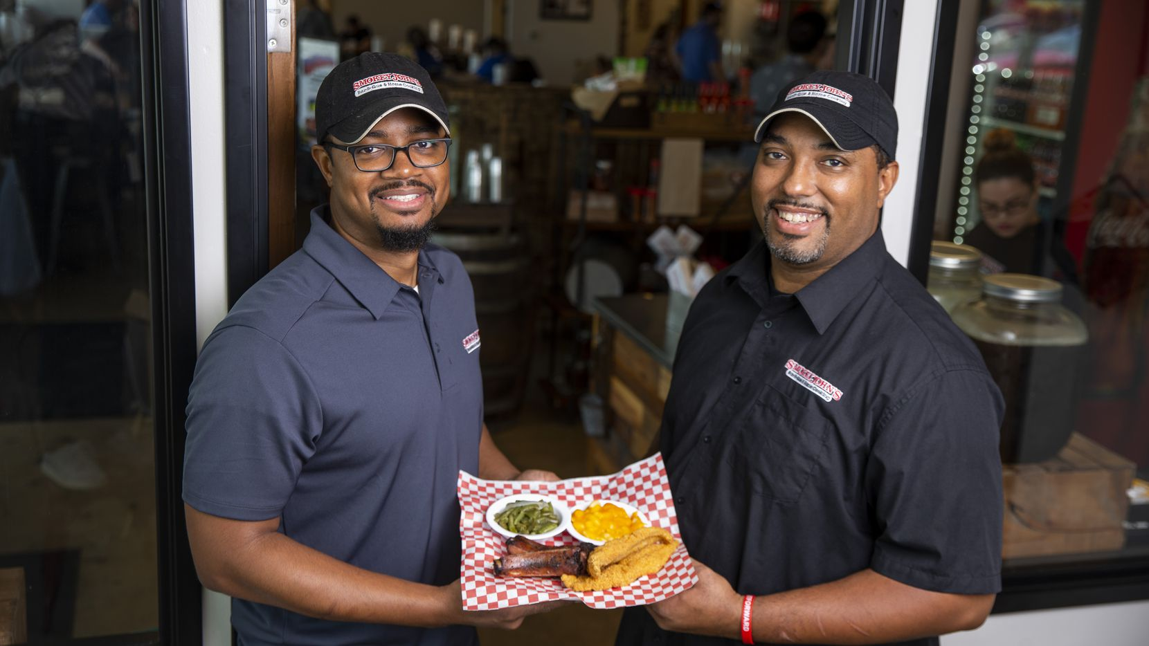 Brent (left) and Juan Reaves hold The Steve White, which is two catfish fillets, two ribs, green beans and mac and cheese, priced at $14.95 at Smokey John's Bar-B-Que and Home Cooking in Dallas on June 26, 2019. (Shaban Athuman/Staff Photographer)