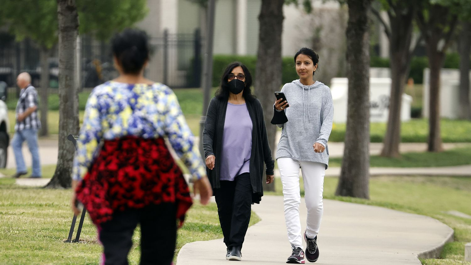 Neighbors living around Lago de Claire lake in the Las Colinas area of Irving, Texas, stroll along a lake path with and without masks, Tuesday, April 27, 2021.