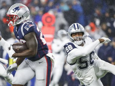 Dallas Cowboys defensive end Robert Quinn (58) is unable to stop New England Patriots running back Sony Michel (26) during the first half of an NFL matchup between the New England Patriots and the Dallas Cowboys at Gillette Stadium in Foxborough, Massachusetts on Sunday, Nov. 24, 2019.