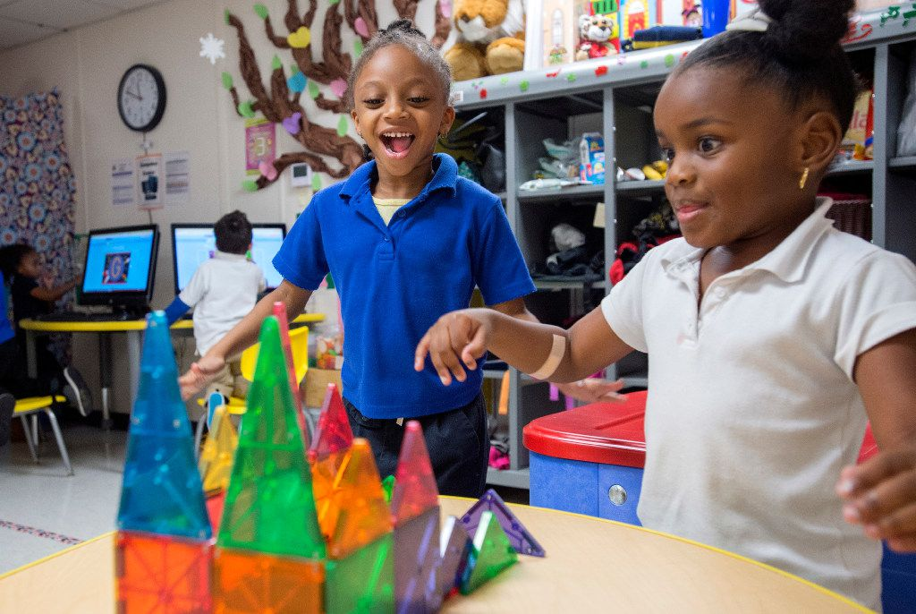 Pre-K students Nariah Odom, 4, and Alexis Rowden, 5, celebrate the completion of their magnetic block structure at Dallas ISD's Wilmer Early Childhood Center.
