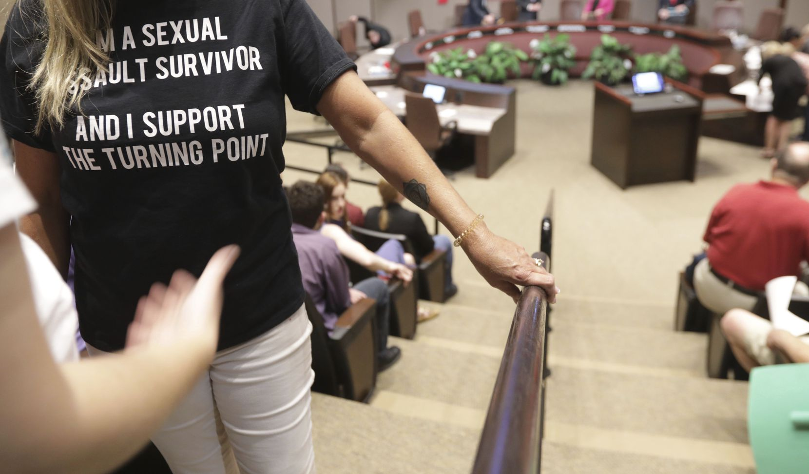 """A person wearing a t-shirt saying """"I am a sexual assault survivor"""" waits to speaks in support of The Turning Point rape crisis center, during the Plano City Council meeting on Monday, Aug. 12, 2019 in Plano, Texas."""