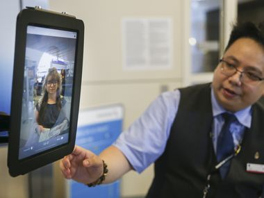 Gate agent Steven Phu assists as passengers board an American Airlines flight to Tokyo Narita International Airport using facial biometric scanning Tuesday, Aug. 27, 2019 in Terminal D of DFW Airport. The iPad device, which is currently only in use for international travelers, matches faces with the U.S. Customs and Border Protection (CBP) database, which includes passport photos. The information collected is transmitted only to CBP and not to independent airlines.
