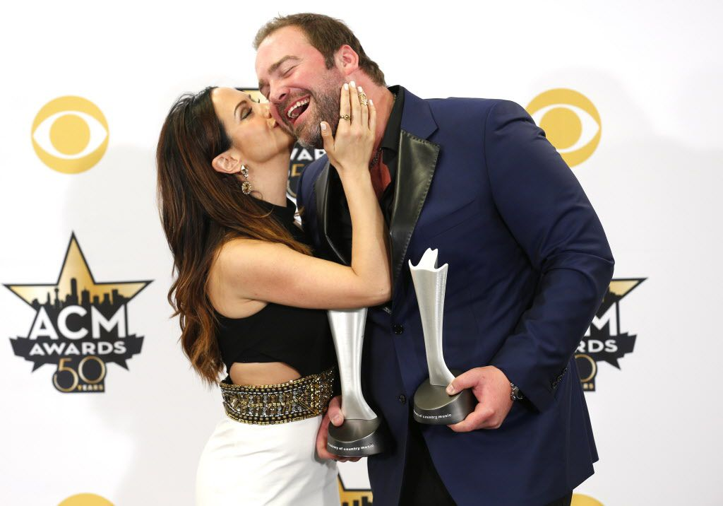 Lee Brice get a kiss from his wife Sara while posing for a photo with his awards during the 2015 Academy of Country Music Awards Sunday, April 19, 2015 at AT&T Stadium in Arlington, Texas.