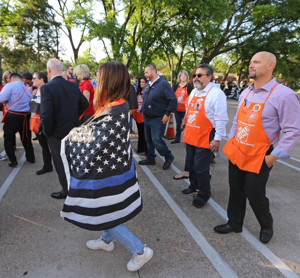 A busload of Home Depot employees arrives at a candlelight vigil to support Dallas Police Officer Crystal Almeida, and to honor the memory of Officer Rogelio Santander, Jr., held at the Dallas Police Northeast Division substation on Thursday, April 26, 2018.