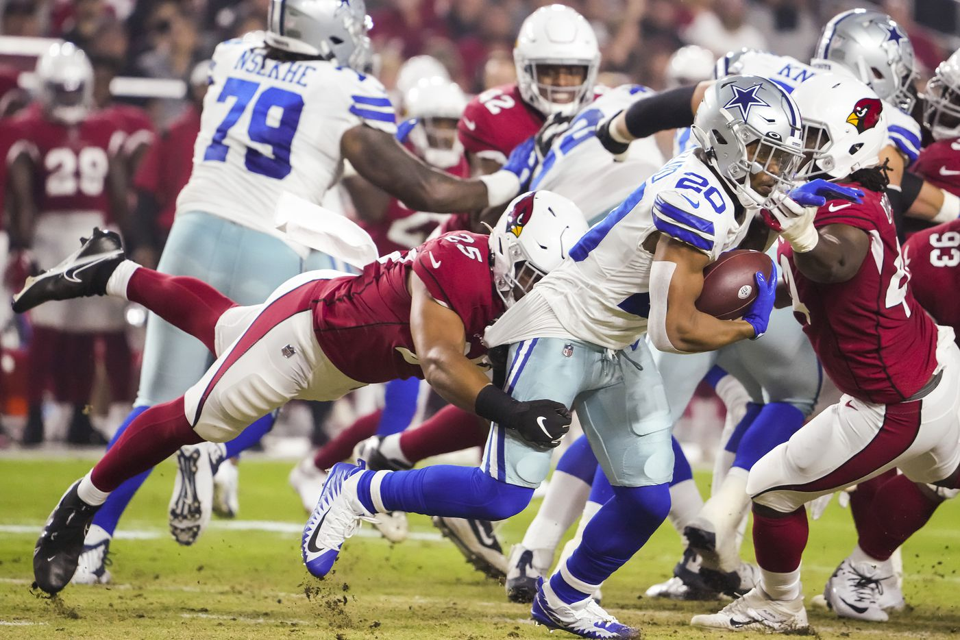 Dallas Cowboys running back Tony Pollard (20) is brought down by Arizona Cardinals linebacker Zaven Collins (25) behind the line of scrimmage during the first quarter of an NFL football game at State Farm Stadium on Friday, Aug. 13, 2021, in Glendale, Ariz.