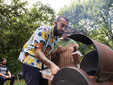 Usama Khalid mans a grill as he finishes cooking Seekh Kebabs and toasting nan during a PunjabiTex BBQ popup at Sweet Pass Sculpture Park in Dallas, on Saturday, Aug. 14, 2021.