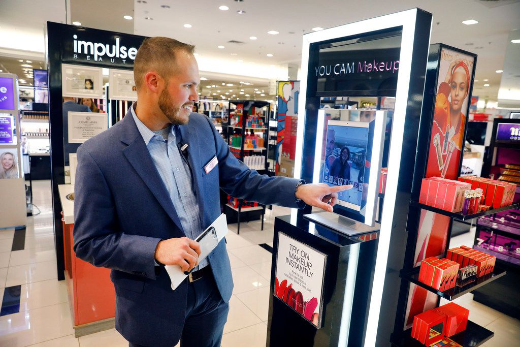 NorthPark Macy's vice president/store manager Josh Adkins demonstrates how the You Cam Makeup kiosk works.  The kiosk is one of the upgrades to the cosmetics department.