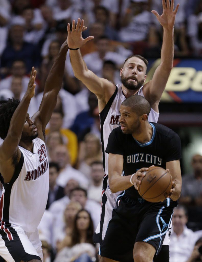 Charlotte Hornets guard Nicolas Batum looks for an open teammate past Miami Heat forward Justise Winslow (20) and forward Josh McRoberts, rear, during the second half in Game 5 of an NBA basketball playoffs first-round series, Wednesday, April 27, 2016, in Miami. The Hornets defeated the Heat 90-88. (AP Photo/Wilfredo Lee)