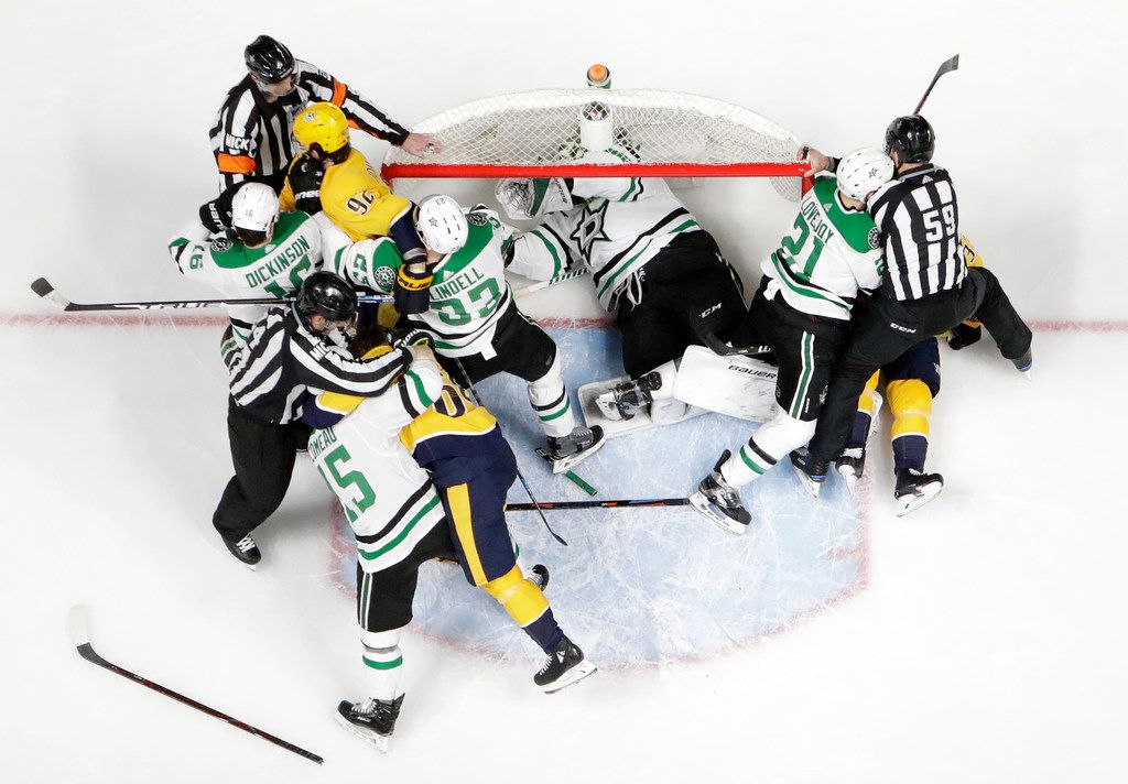 Dallas Stars goaltender Ben Bishop takes refuge in the net as players fight during the first period in Game 2 of an NHL hockey first-round playoff series against the Nashville Predators, Saturday, April 13, 2019, in Nashville, Tenn. (AP Photo/Mark Humphrey)