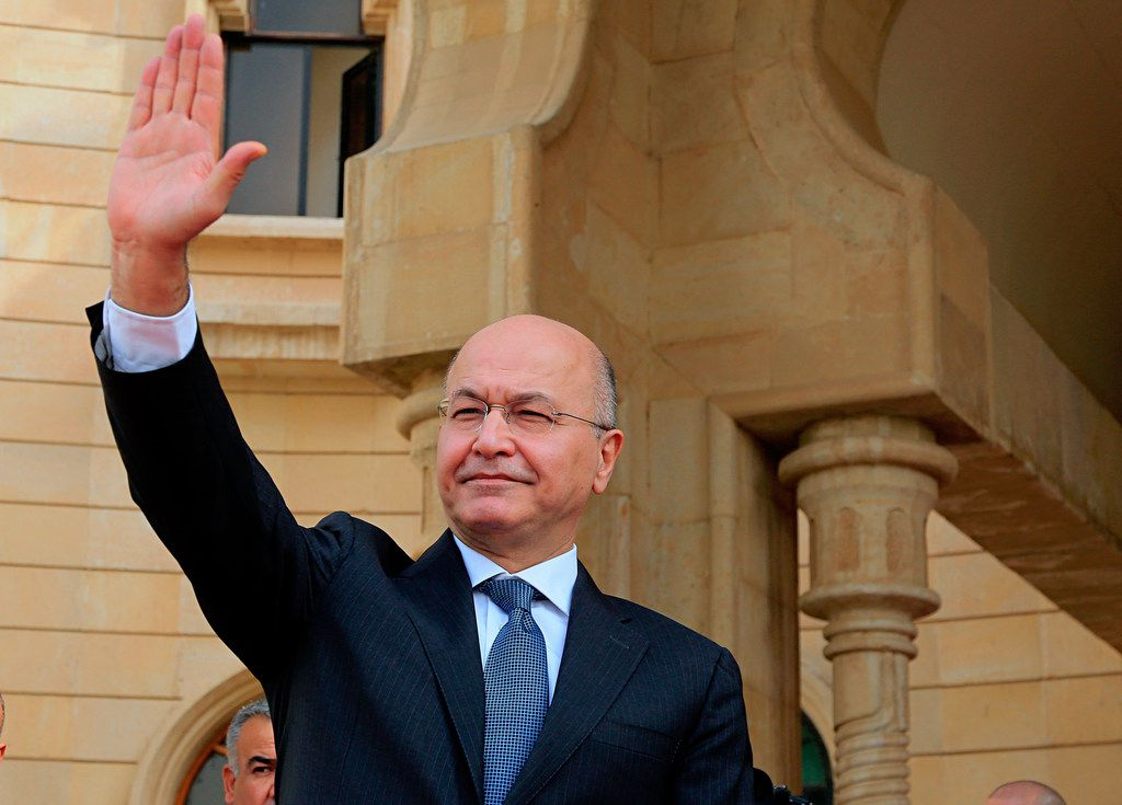 In this Oct. 11, 2018 file photo, Iraqi President Barham Salih waves goodbye to Turkish Foreign Minister Mevlut Cavusoglu, after their meeting in Baghdad, Iraq.