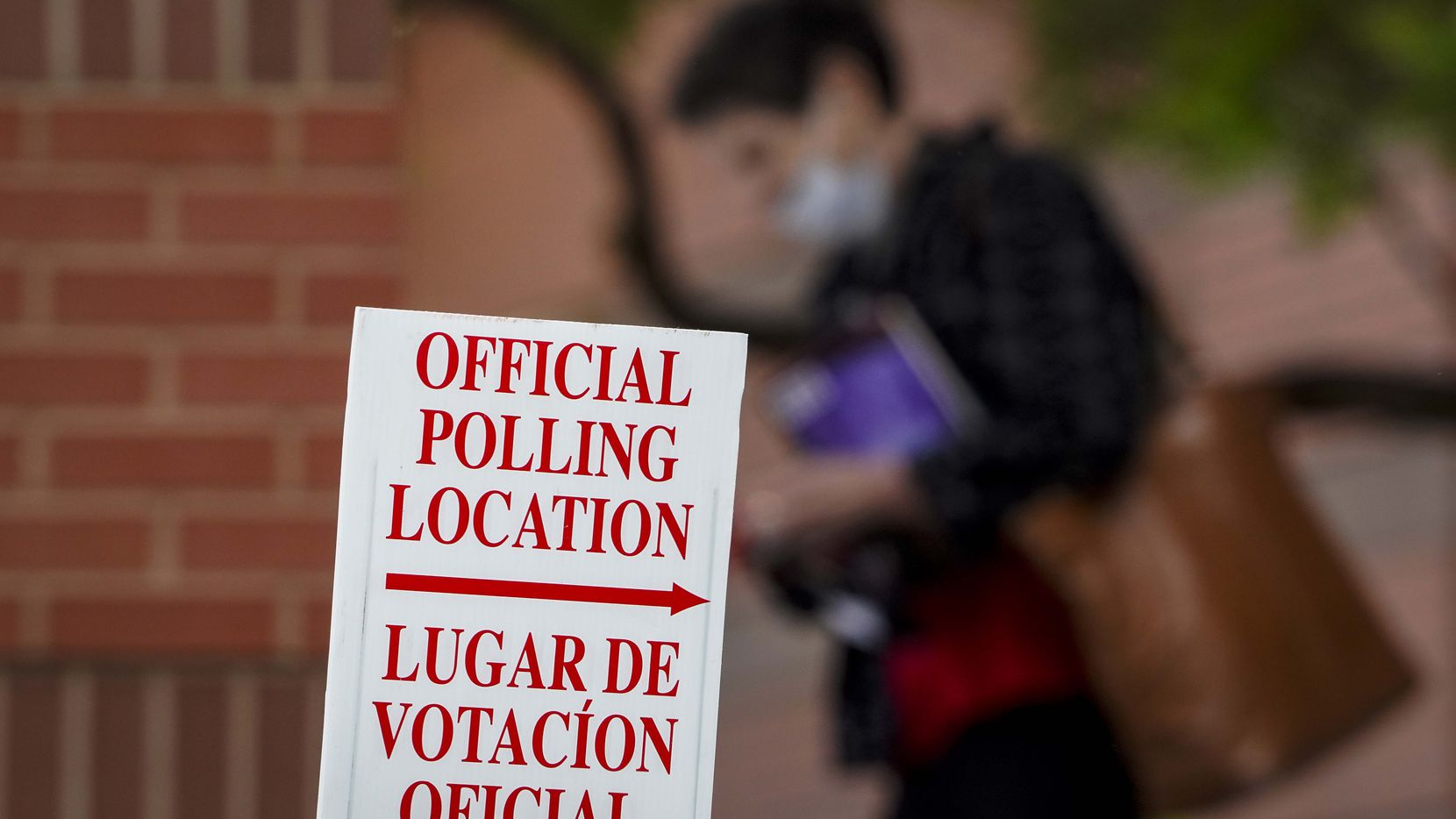 A woman wearing a face mask passes a polling place sign outside a Collin County Early Voting Location at Carpenter Park Recreation Center on June 29, 2020, in Plano. (Smiley N. Pool/The Dallas Morning News)