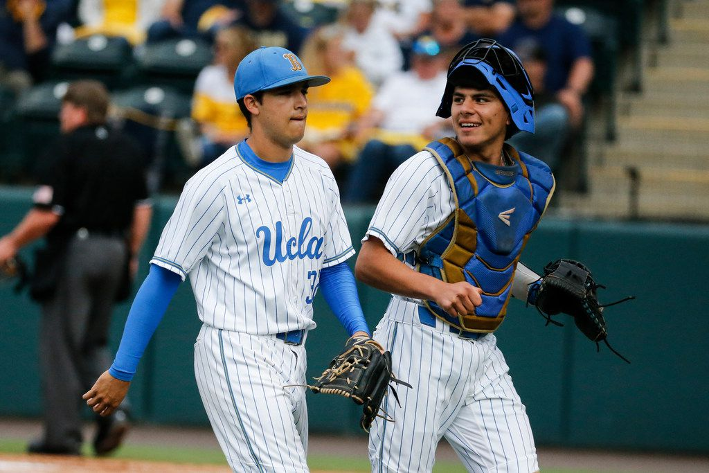 UCLA pitcher Ryan Garcia, left, and catcher Noah Cardenas walk off the field after the top of the first inning of the team's NCAA college baseball tournament super regional game against Michigan in Los Angeles, Friday, June 7, 2019. (AP Photo/Ringo H.W. Chiu)