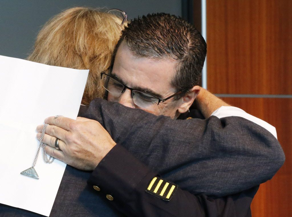 Marcia Davis (left) of Plano, representing Point 27, a Georgia faith-based nonprofit agency, hugs Executive Assistant Chief David Pughes after donating 3,200 Thin Blue Line silver Scripture-inscribed Shields of Strength. (David Woo/Staff Photographer)