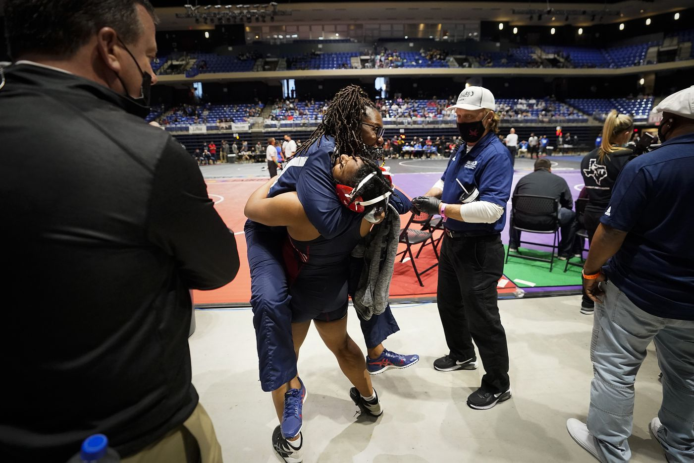 Ki`Aundra Green of Dallas Kimball lifts coach Nicholet Singh in celebration after defeating Noemi Gonzalez of Corpus Christi King in a third place in the 5A girls 185-pound weight class during the UIL State Wrestling tournament at the Berry Center on Friday, April 23, 2021, in Cypress, Texas.