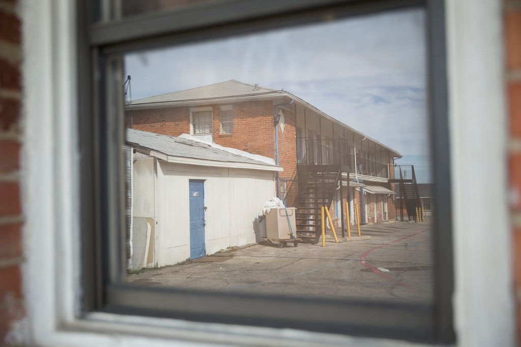 The two-story building of Cole Manor Motel is reflected on a motel window.
