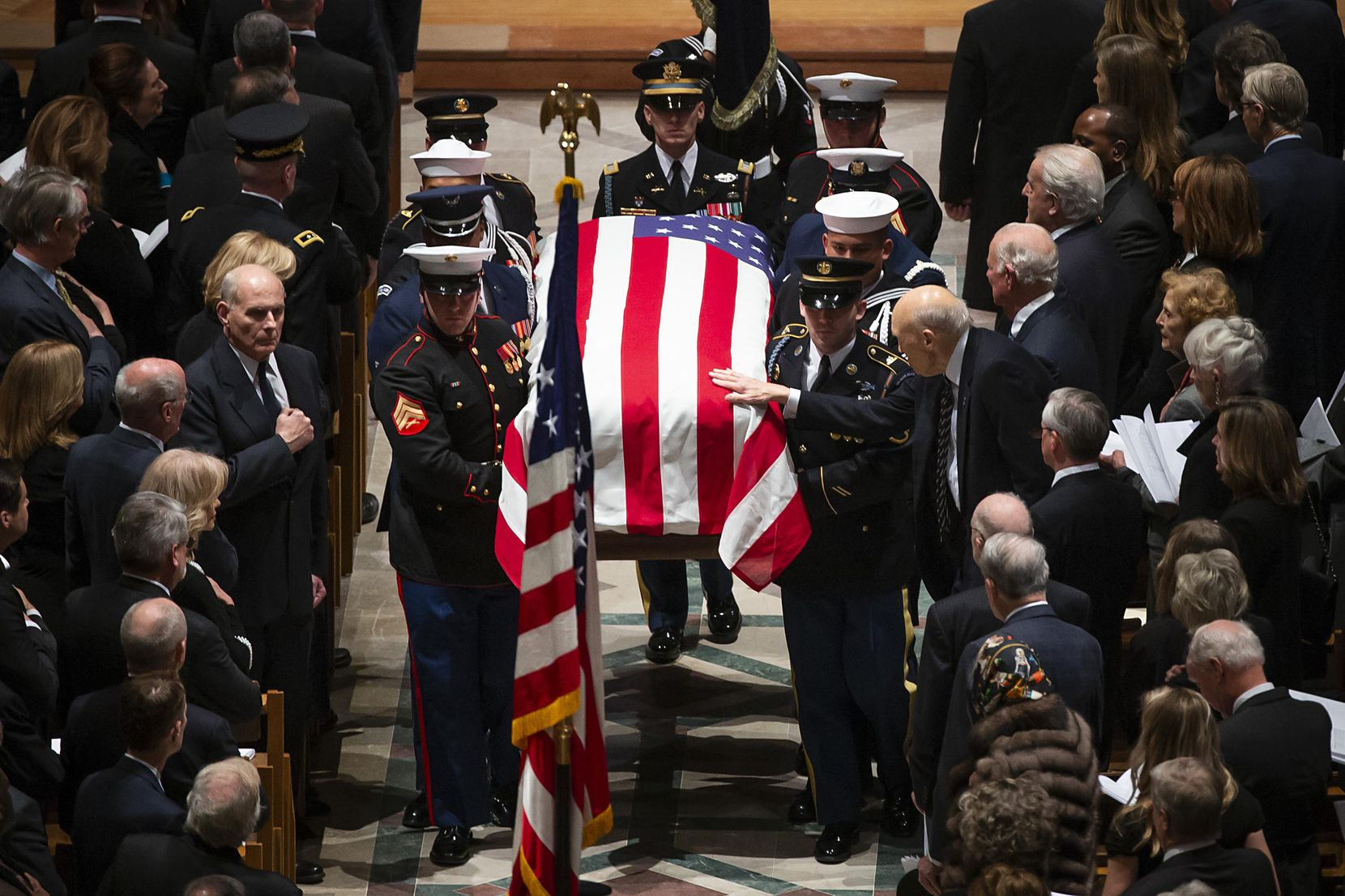Former Sen. Alan Simpson reached out to touch the flag-draped casket of his friend as a military honor guard carried it from the Washington National Cathedral after Wednesday's state funeral.