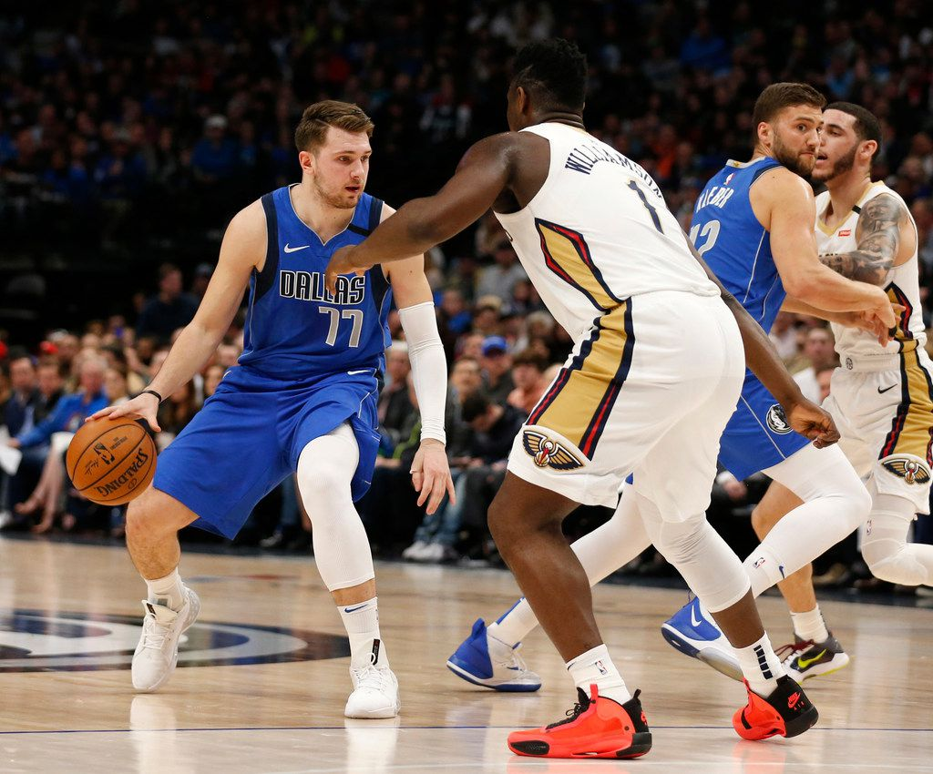 Dallas Mavericks guard Luka Doncic (77) dribbles in front of New Orleans Pelicans forward Zion Williamson (1) during the first quarter of play at American Airlines Center in Dallas on Wednesday, March 4, 2020.