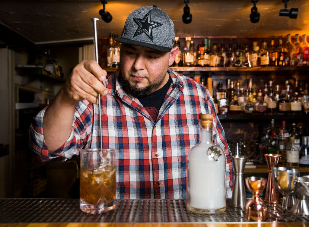 Mixologist Manny Casas mixes cocktail ingredients together in a mixing pitcher.
