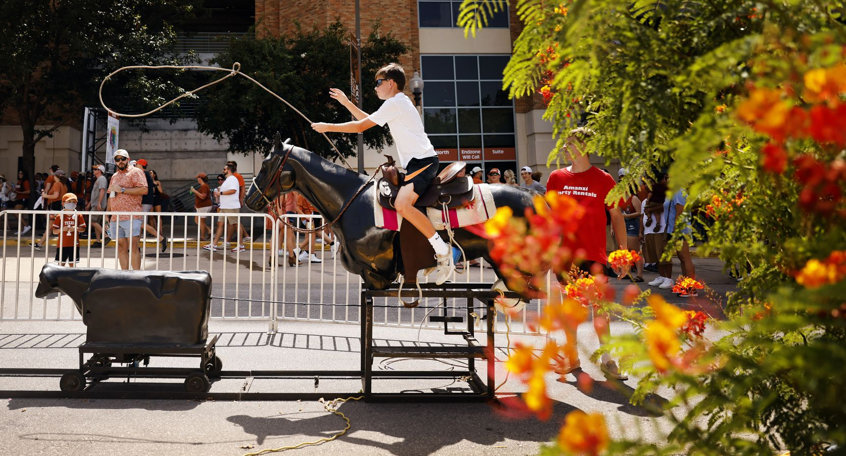 Gavin Thornfield of Dallas tries to lasso a mechanical calf on Smokey's Midway, a mini 'state fair' outside of DKR-Texas Memorial Stadium in Austin, Saturday, September 4, 2021. The Longhorns were facing the Louisiana-Lafayette Ragin Cajuns. (Tom Fox/The Dallas Morning News)