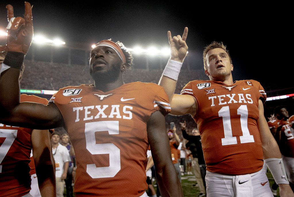 "Texas defensive back D'Shawn Jamison (5) and quarterback Sam Ehlinger (11) hold up the ""Hook 'em Horns"" sign for the playing of ""The Eyes of Texas"" following Texas' 36-30 win over Oklahoma State during an NCAA college football game Saturday, Sept. 21, 2019, in Austin, Texas. (Nick Wagner/Austin American-Statesman via AP)"
