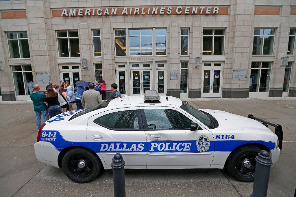 A Dallas Police car is parked in front of the entrance to American Airlines Center as fans line up before a concert. )