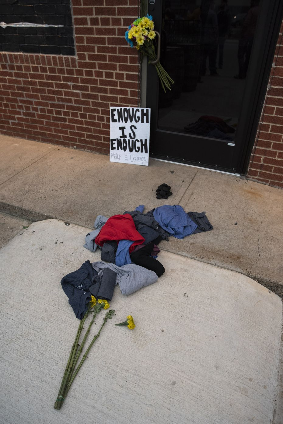Piles of clothes, coal and flowers were placed outside the entrance to Redfield's Tavern in Dallas during a protest, on Saturday, Oct. 24, 2020.