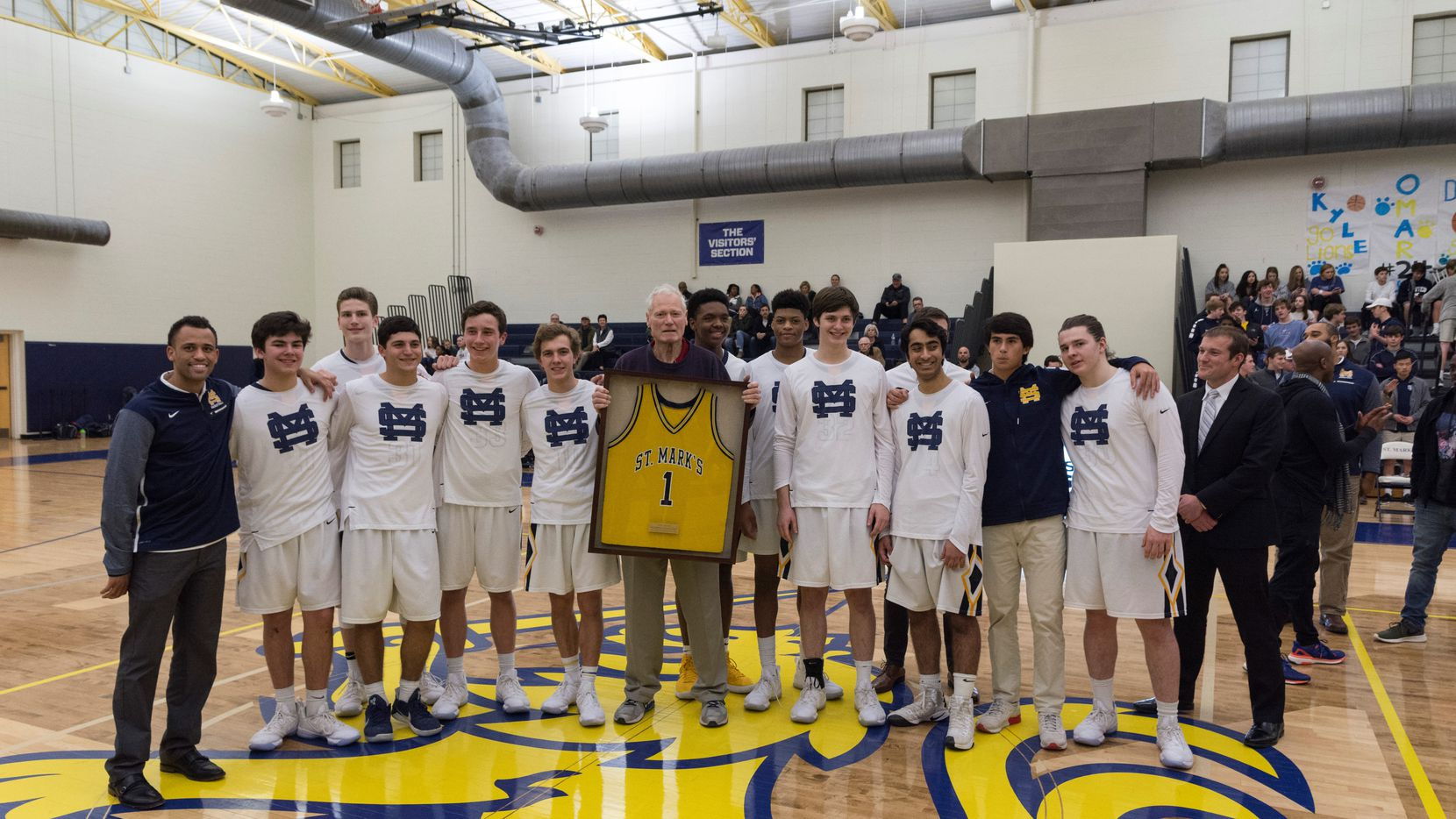 Tom Adams (center, holding jersey) was honored in 2018 during the final season that he worked as an assistant coach for the St. Mark's basketball team.