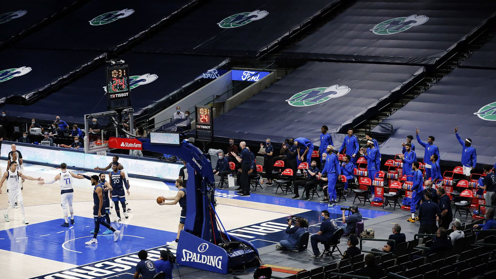 Before the empty stands of American Airlines Center, Mavericks guard Luka Doncic (77) is congratulated by teammates after drawing a foul in a preseason game against the Timberwolves on Thursday, Dec. 17, 2020. It was the first Mavs game inside the arena since the NBA shutdown earlier this year to COVID-19.