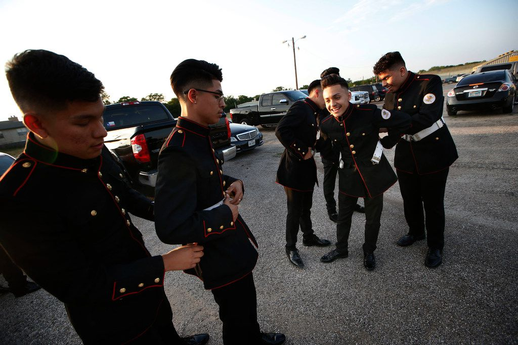 Marco Barajas (second from left) gets help from a fellow cadet with his suit. The teens start their night getting ready in a parking lot.