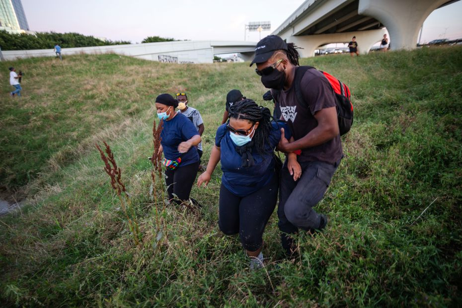 Protesters running from popping sounds near Interstate 35 on the west side of downtown Dallas help a woman who has fallen.