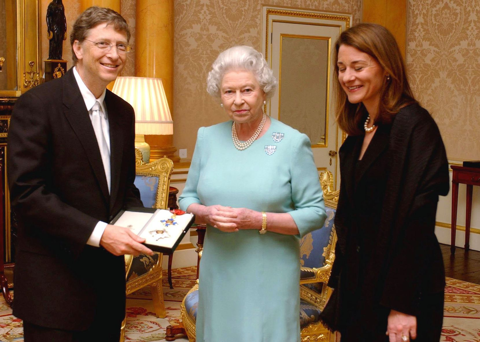 """Britain's Queen Elizabeth II presents Microsoft tycoon Bill Gates with his honorary knighthood at Buckingham Palace, London, Wednesday, March 2, 2005, watched by his wife Melinda. Gates, one of the richest men in the world, cannot use the title """"Sir"""" as he is not a British citizen. He received the KBE insignia, in recognition of his charitable donations in Commonwealth countries.      AFP PHOTO/CHRIS YOUNG/WPA POOL"""