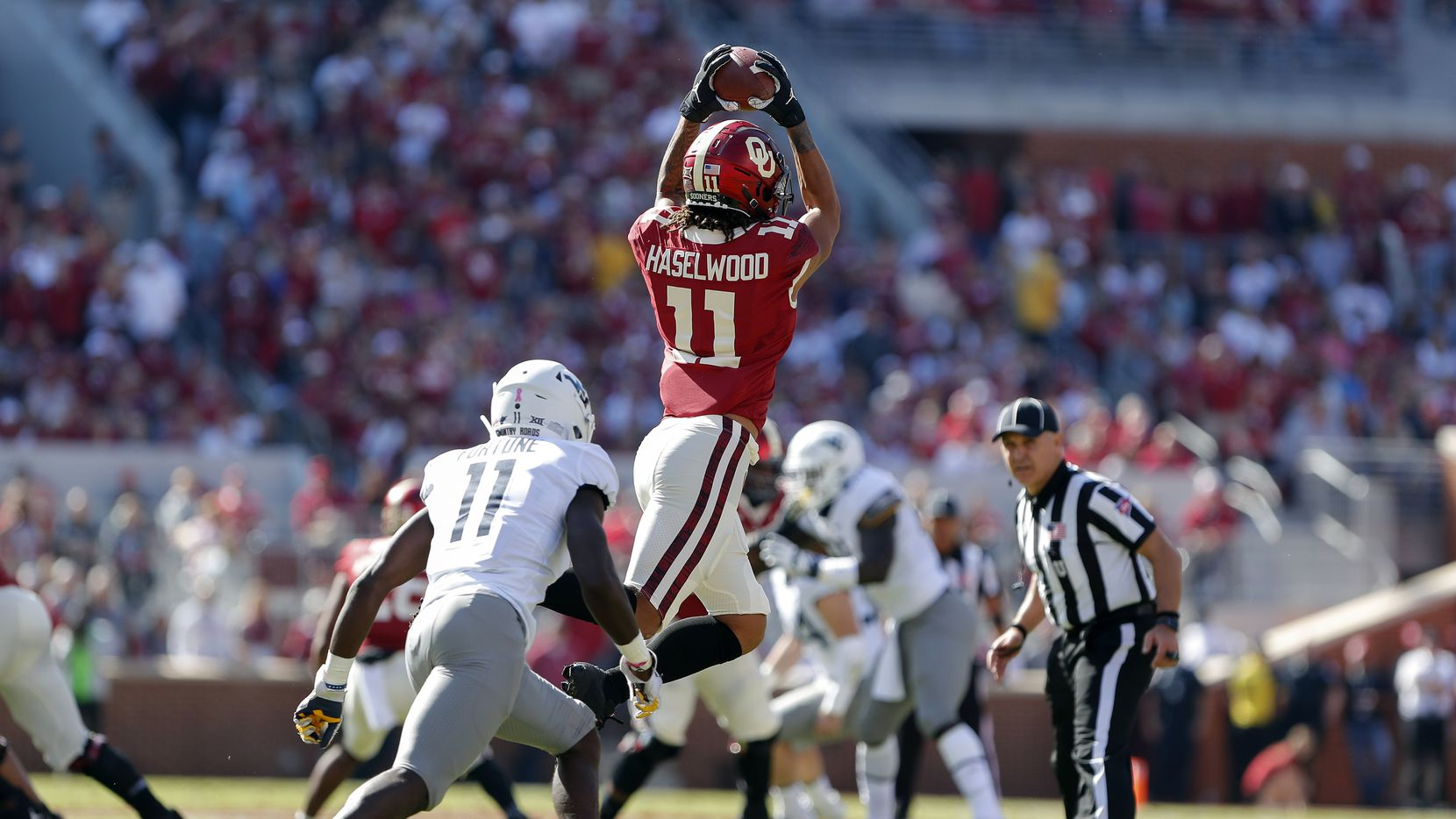 Oklahoma wide receiver Jadon Haselwood (11) makes a catch ahead of West Virginia cornerback Nicktroy Fortune (11) during the first half of an NCAA college football game in Norman, Okla., Saturday, Oct. 19, 2019.
