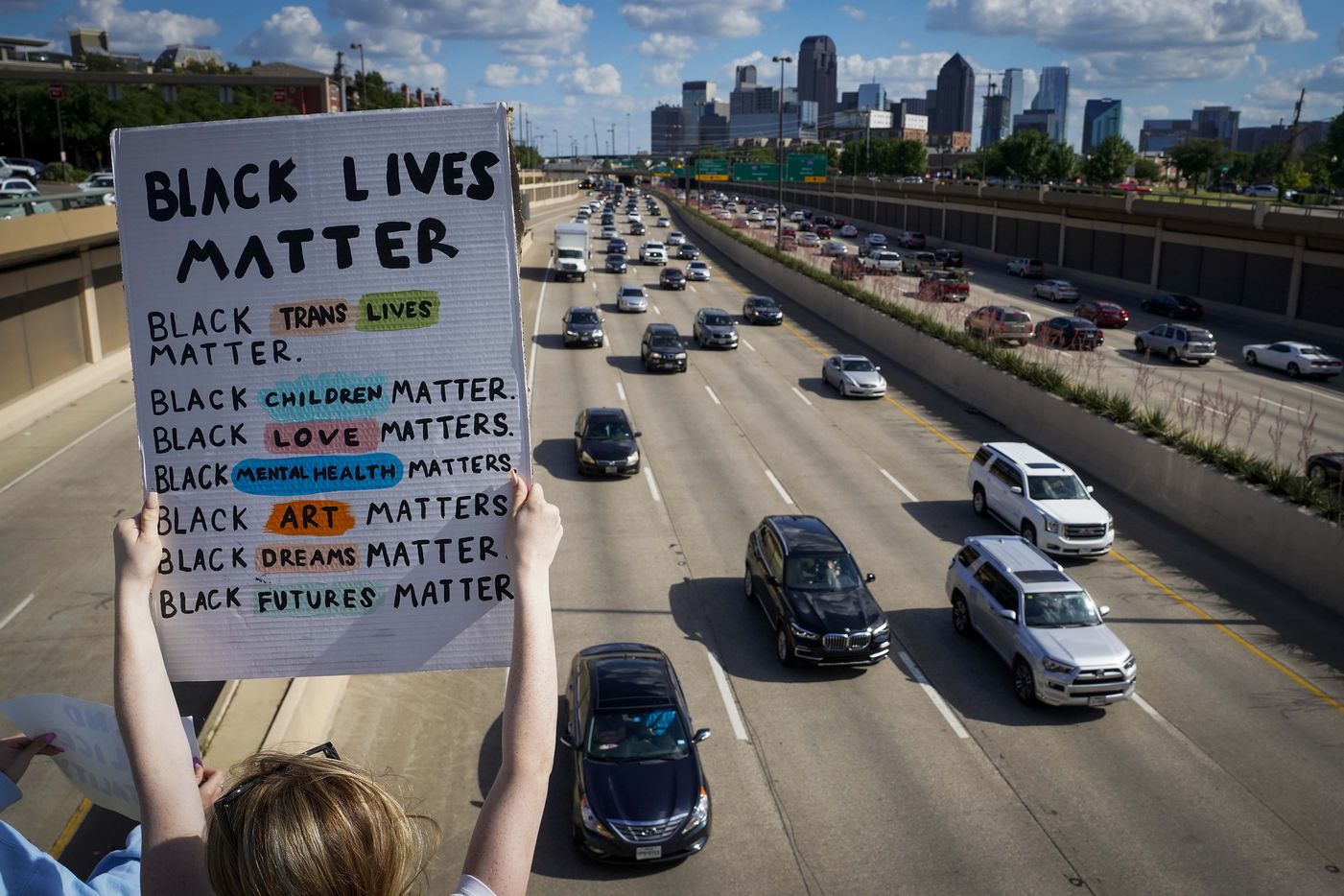 Protesters hold signs for rush hour motorists headed north out of downtown from the Lemmon Avenue bridge over US-75 Central Expressway on Friday, June 5, 2020, in Dallas. Protests continued Friday in the response to the death of George Floyd.