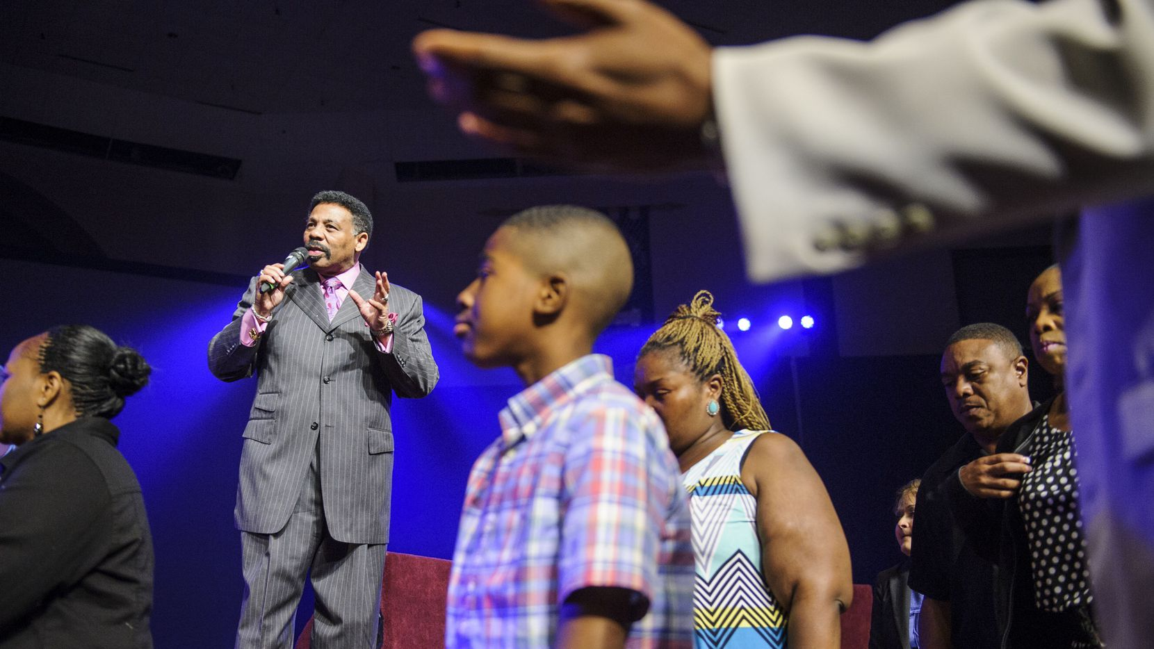"""Pastor Dr. Tony Evans talks to the congregation as his ministers lead a group to a side room for additional prayer during Oak Cliff Bible Fellowship's presentation of, """"The Greatest Doubt,"""" on Easter Sunday, April 20, 2014."""