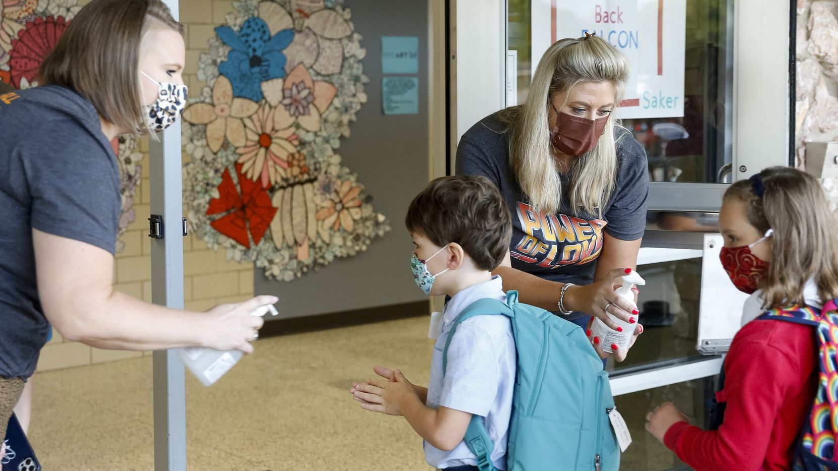 Assistant principal Catherine Bennett (left) and principal Kristin Strickland squirted sanitizer onto students hands as they arrived Tuesday for the first day of school at Arapho Classical Magnet in Richardson.