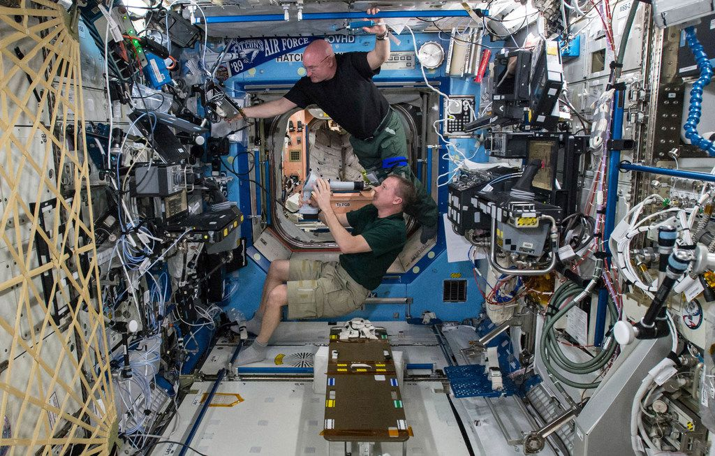 On April 9, 2015, astronauts Terry Virts (bottom) and Scott Kelly perform eye exams in the Destiny Laboratory of the International Space Station as part of studies on vision health in microgravity.