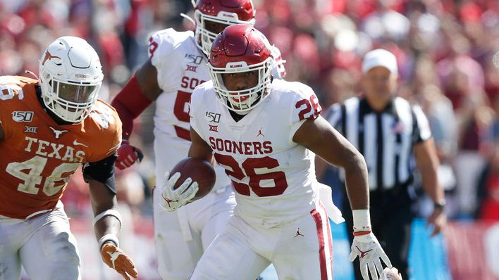 Oklahoma Sooners running back Kennedy Brooks (26) shakes Texas Longhorns defensive back B.J. Foster (25) on a play as Texas Longhorns linebacker Joseph Ossai (46) closes in on him during the second half of play in the Red River Showdown at the Cotton Bowl in Dallas on Saturday, October 12, 2019.