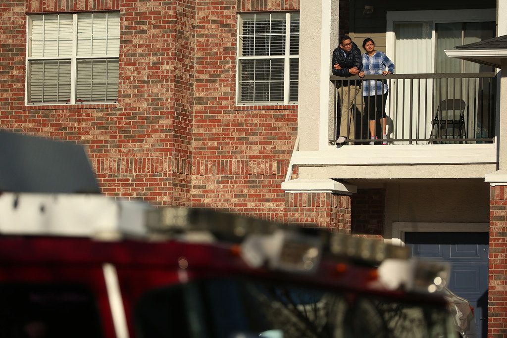 Individuals watch from a balcony as authorities work near where they suspect Brandon McCall shot an officer the day before at the Breckinridge Point apartment complex in Richardson, Texas Thursday, February 8, 2018. Brandon McCall, a 26-year-old with a history of run-ins with police, has been charged with capital murder of a peace officer after a Richardson officer was fatally shot while responding to a disturbance call at the Breckinridge Point apartment complex.